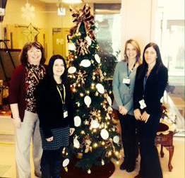 Organizers (l-r) Deanne Clancey, Recreation Therapist; Laurie Adams, Recreation Specialist; Joanne Hanlon, Occupational Therapist; and Tennille Blackwood, Occupational Therapy Assistant; next to one of the Kris Kringle Trees.