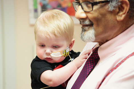 Dr. Shah holding baby Jacob at the Janeway Cardiology Clinic's Open House. Photo by Phil Simms.