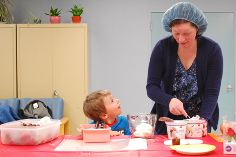 John helping Lisa create dips at the cooking class