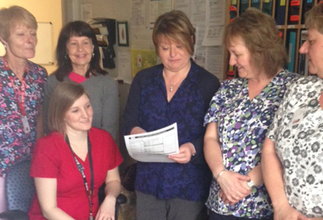 Outbreak Management briefing at Hoyles-Escasoni. Standing (l-r): Dianne Petten, LPN; Joan Decker, Environmental Services Supervisor; AnnMarie Penney, IPAC; Sandra McCarthy, Environmental Services; Pam Noseworthy, Medical Services Aide. Seated: Melissa Badcock, B.N., R.N.