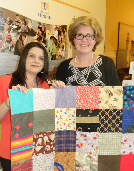 Janice Dalton, member of the Ocean View Quilters Guild and regional coordinator for Eastern Health's long-term care program presents touch quilts to Laurie Adams, recreation specialist at the Hoyles-Escasoni Complex.