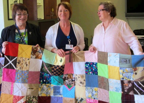 (l-r) Cathie Barker Pinsent, regional manager of Eastern Health's Personal Care Home Program, and Judy Peddle, program coordinator of Eastern Health's Personal Care Home Program, receive touch quilts from Margaret Wade, member of the Ocean View Quilters Guild.