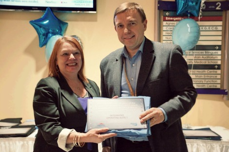 Elizabeth Harding accepting a plaque and honourary scrubs from Eastern Health President and CEO David Diamond on behalf of the RDTC at the naming ceremony for the Integrated Operating Suites