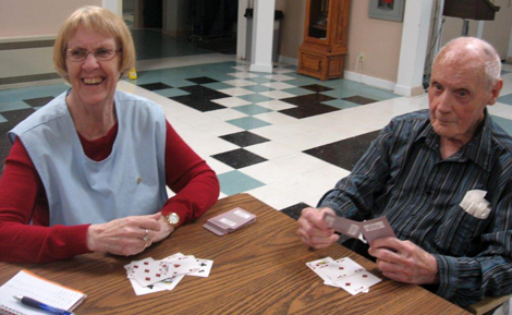 (l-r): Volunteer Joyce Matchem and resident, Lewis Byrne, playing cards