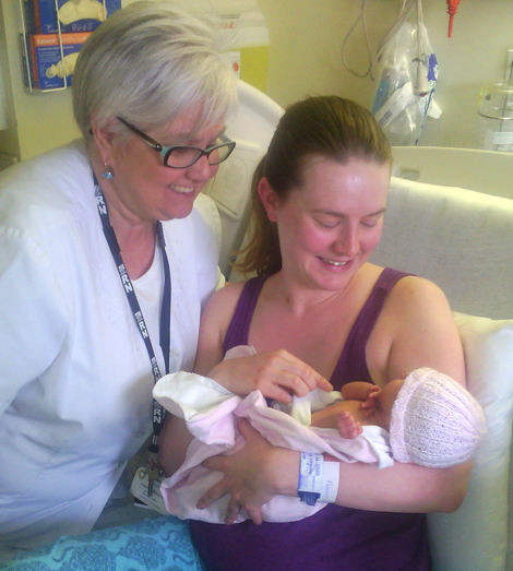Corinne Bursey assisting new mother and her baby with breastfeeding