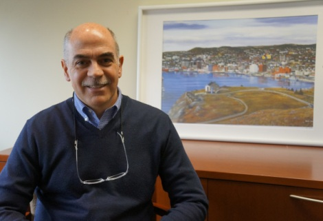 Dr. Gai sits in LMP Medical Director, Dr. Chetty's office, with a painting of St. John's, Newfoundland featured in the background.