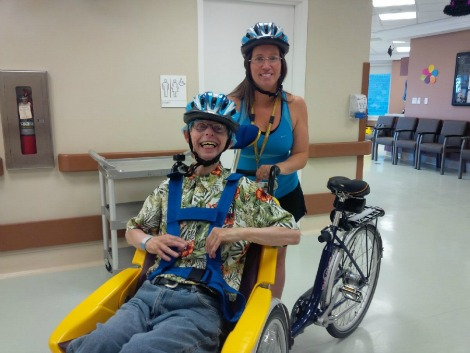(l-r) Long-term resident David Makinson (deceased) enjoyed indoor time on the Duet bike with Therapeutic Recreation Development Specialist Nancy Hodder.