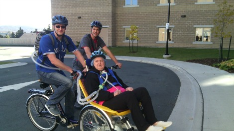 (l-r): Therapeutic Recreation Development Specialist Tim Colbourne and resident Elizabeth Matthew on the duet bicycle outside the St. John's Long-Term facility. Back: Nurse Craig Heffernan rides along to provide medical support.