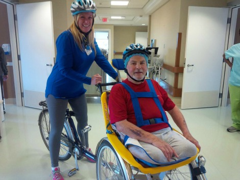 (l-r): Therapeutic Recreation Development Specialist Rebecca Maloney and resident Kevin Hynes, riding the duet bicycle indoors at the St. John's Long-Term Care facility