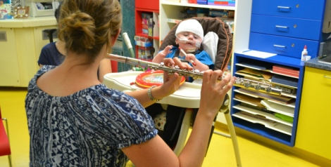 Music therapist, Susan LeMessurier Quinn, plays flute to a contented Graysen. (Photo with permission for Janeway Child Life Department)