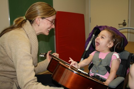Young patient, Minxie, shows her guitar skills to music therapist Susan LeMessurier Quinn. (With permission the Janeway Foundation.)