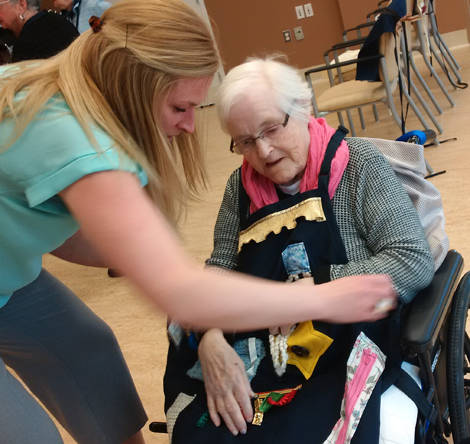 Recreation development specialist Rebecca Maloney fits resident Elsie Legge with a sensory apron
