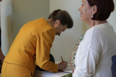 Princess Anne signs the Caribou Pavilion's guest book.