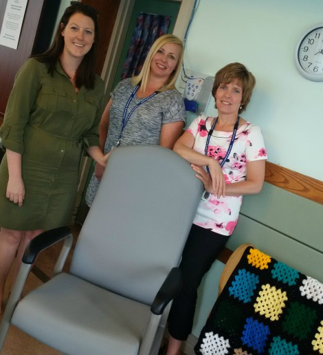 Julie MacDonald and Carmella Butland of the Health Care Foundation, and E2A social worker Tracey Moore with one of 18 donated armchairs.