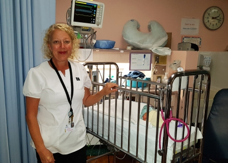 Olive Goobie, lactation consultant and the Janeway Children's Health and Rehabilitation Centre, standing next to a newborn in the Neonatal Intensive Care Unit.