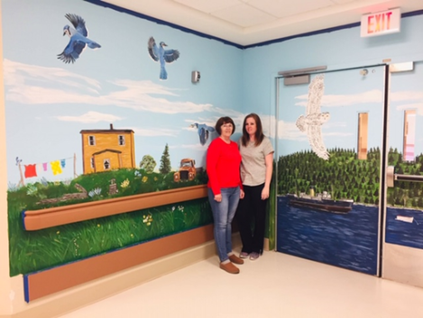 Christa Hogan (right) and her mother, Josephine Hogan, standing in front of the third mural project that is currently in the works.