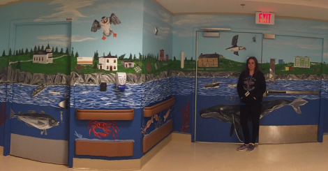 Eastern Health PCA, Christa Hogan, standing in front of the first of many murals at the Private Josiah Squibb Memorial Pavilion